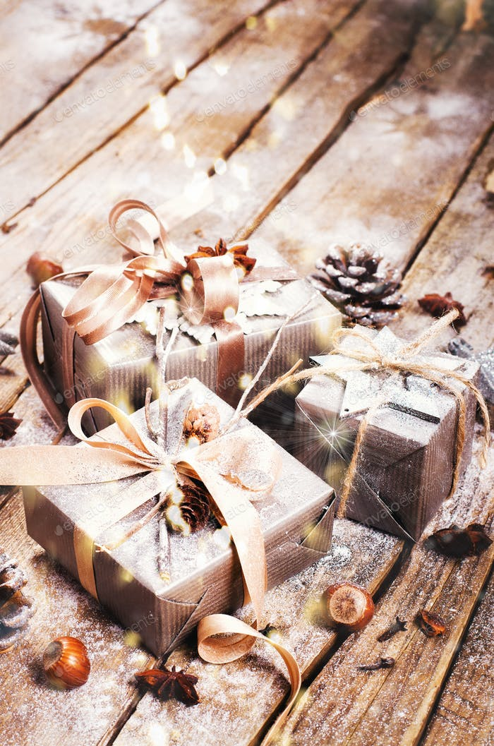 Gift boxes on old wooden background with silver stars, cones, hazelnut, anise, tape, ribbon