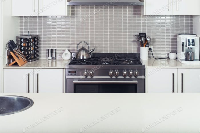 Modern kitchen interior with the stove and utensils with island table