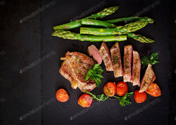 Thumbnail for Juicy steak medium rare beef with spices and tomatoes, asparagus. Top view