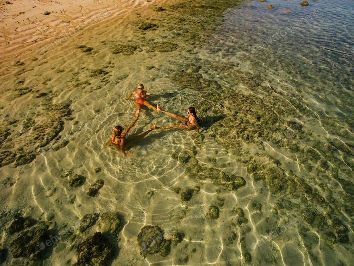 Luftaufnahme von drei jungen Frauen sitzen im Meer