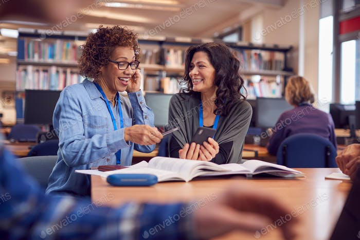 Teacher With Mature Female Adult Student Using Mobile Phone At Table Working In College Library