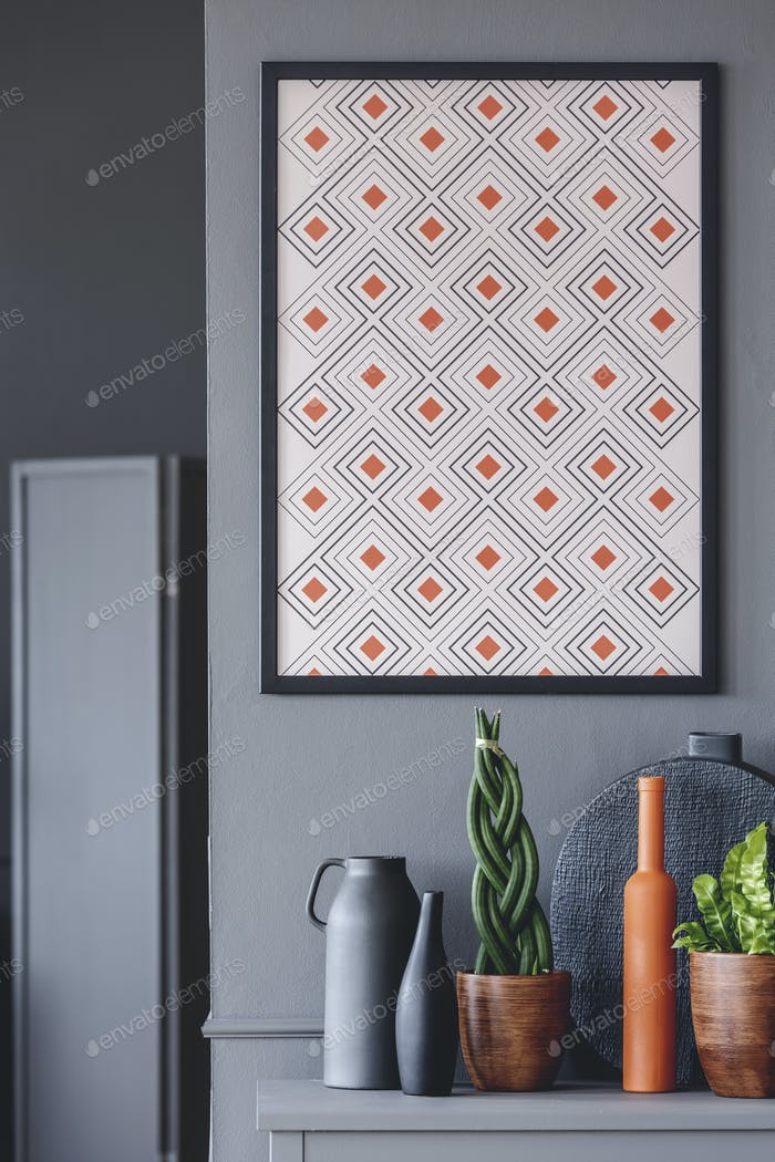 Geometrical poster with orange accents on the wall above plants