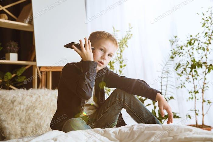 Kleiner Junge mit verschiedenen Gadgets zu Hause
