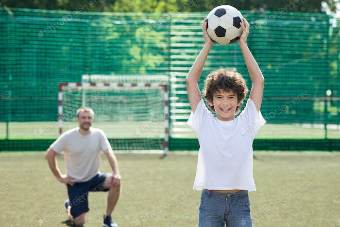 Kleiner Junge posiert mit Fußball auf Fußballplatz