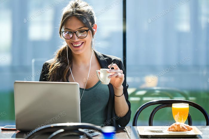 Beautiful young woman drinking coffee while working with her lap