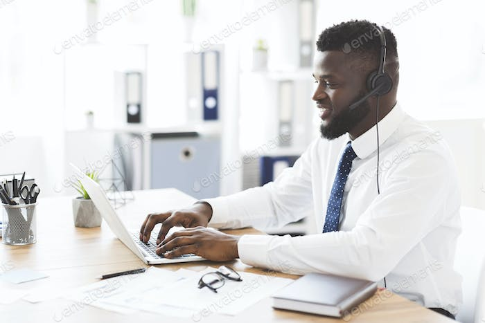 Happy office worker helping clients, using laptop