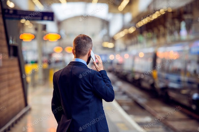 Businessman with smartphone, making a phone call, underground platform