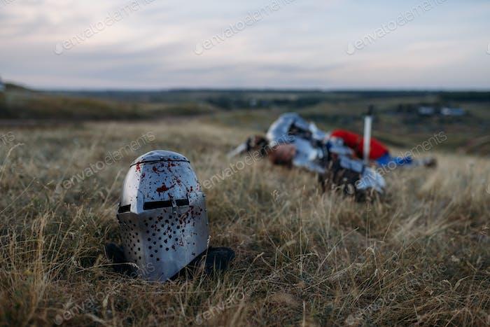 Helmet in blood, dead knight on background