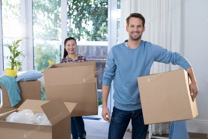 Couple carrying big cardboard box at new home