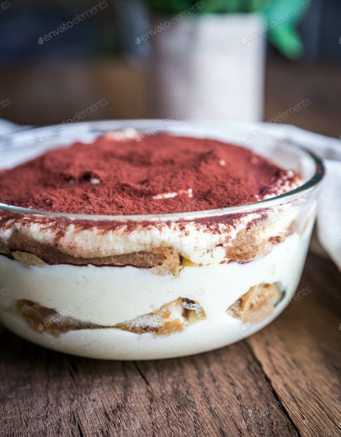 Tiramisu in the glass bowl on the wooden background