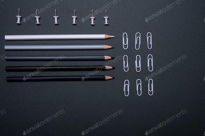 Bunte Bleistifte, Daumenhalter und Clips auf schwarzem Hintergrund
