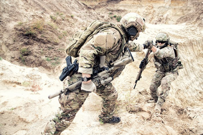 American commando helping friend to climb on dune