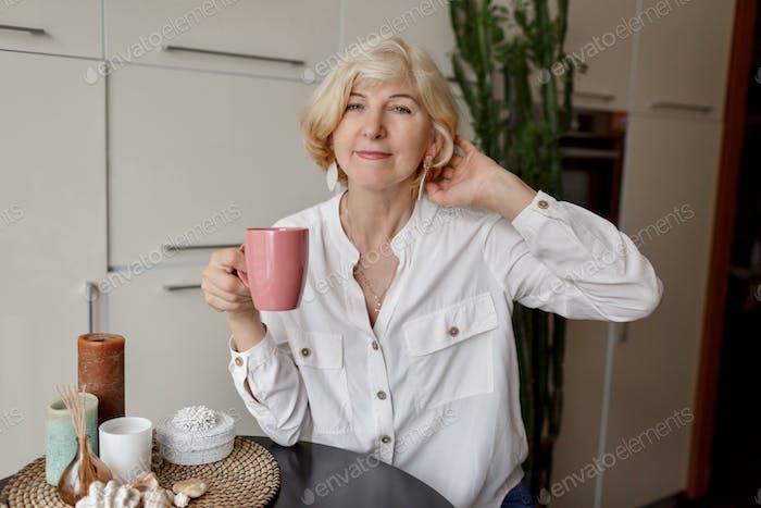 50-jährige blonde Frau hält eine Tasse Tee in der Hand und sitzt in der modernen Küche.