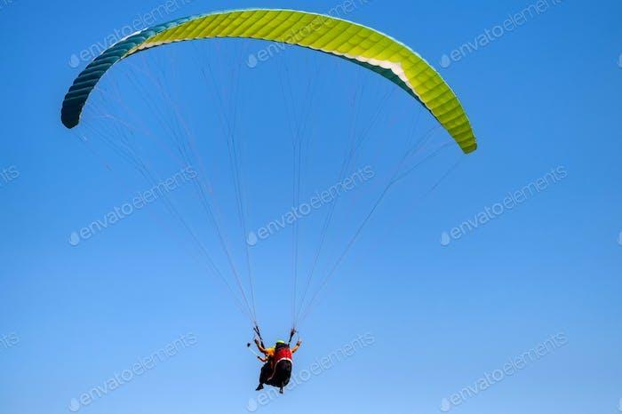 Foto sin nubes de dos personas parapente en el cielo azul