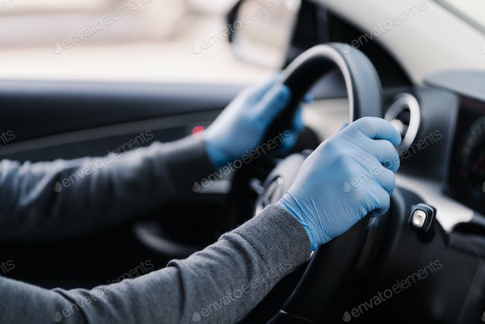 Unrecognizable driver wears rubber protective gloves protects from coronavirus drives car