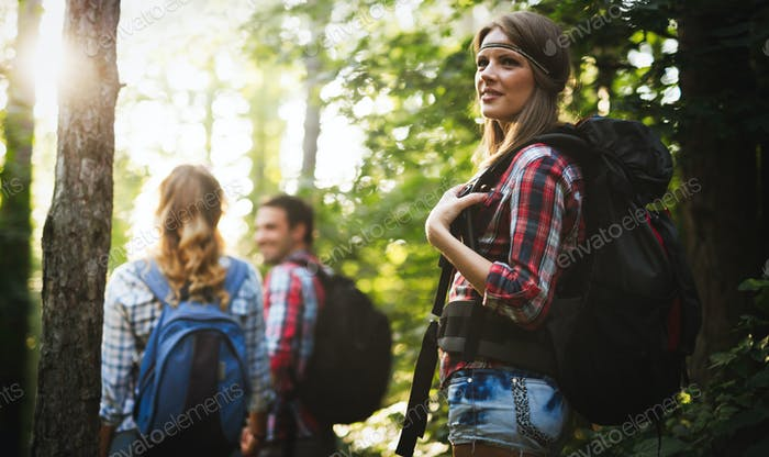 Beautiful woman and friends hiking in forest
