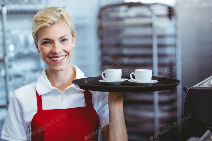 Pretty barista holding two cups of coffee in the cafe