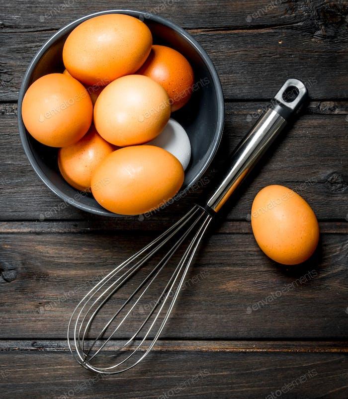 Eier in einer Schüssel mit einem Schneebesen.