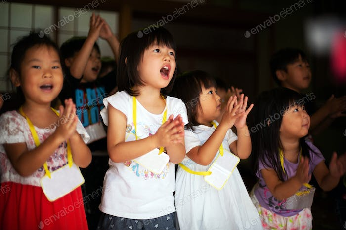 Group of children, girls and boys singing and clapping together in a temple.