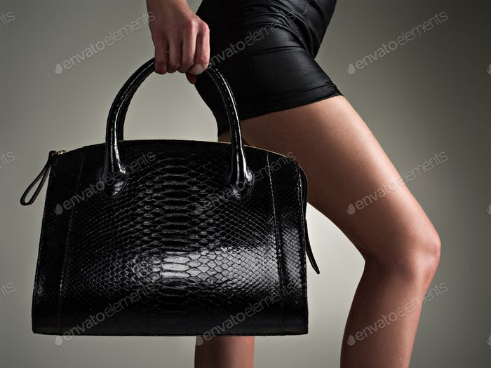Beautiful woman holds stylish black bag. Fashionable girl.