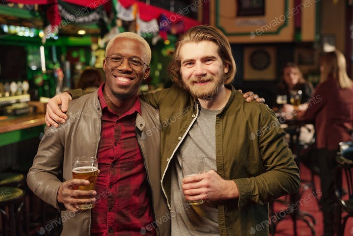 Two young cheerful intercultural men looking at you while toasting with beer