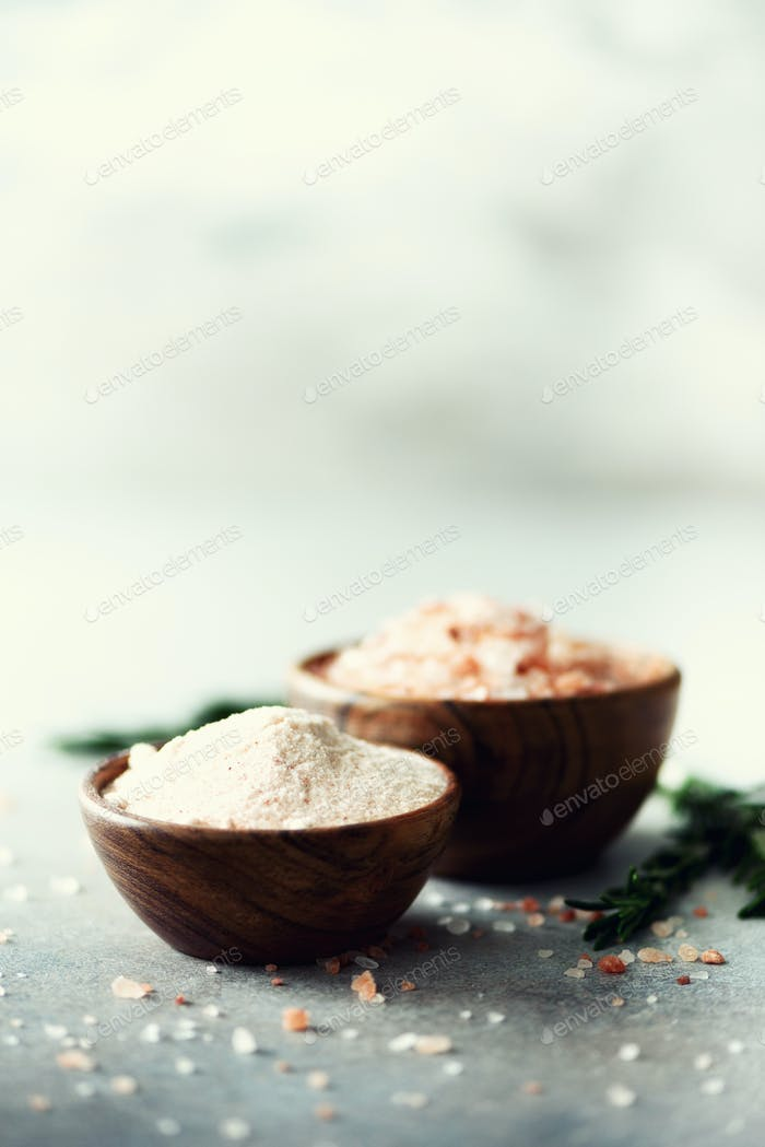 Pink Himalayan salt crystals and powder in wooden bowls with rosemary on grey concrete background