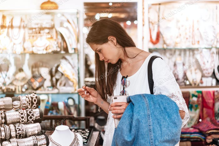 girl chooses jewelry in a jewelry store