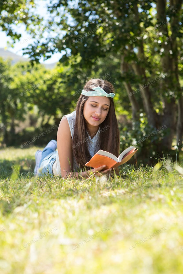 Pretty brunette reading book in the park on a summers day