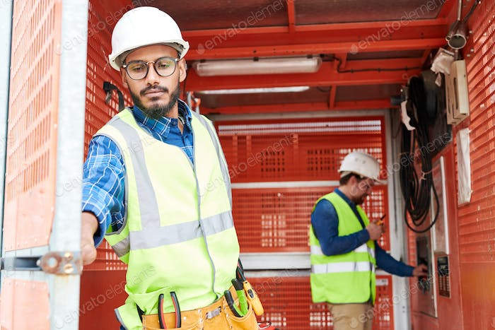 Middle-Eastern Construction Worker Using Transporter