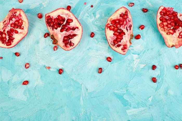 Half pomegranate fruit on blue background. Fresh red ripe