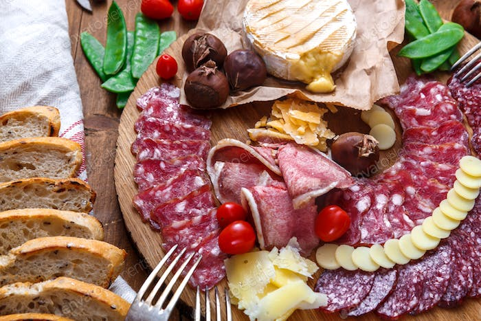 Delisious snacks on wooden board: sausages, bread, cheese, chestnuts and beer. Close view.