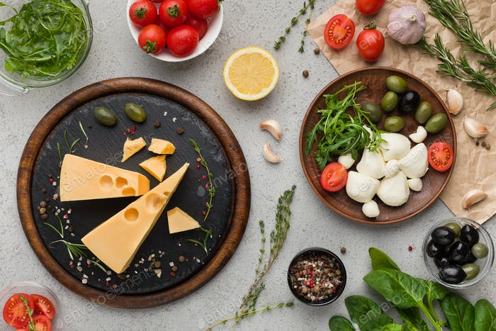 Cheese variety, olives and fresh herbs on grey background