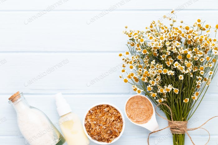 Sea salt, aromatherapy oil in bottles and chamomile on vintage wooden background.