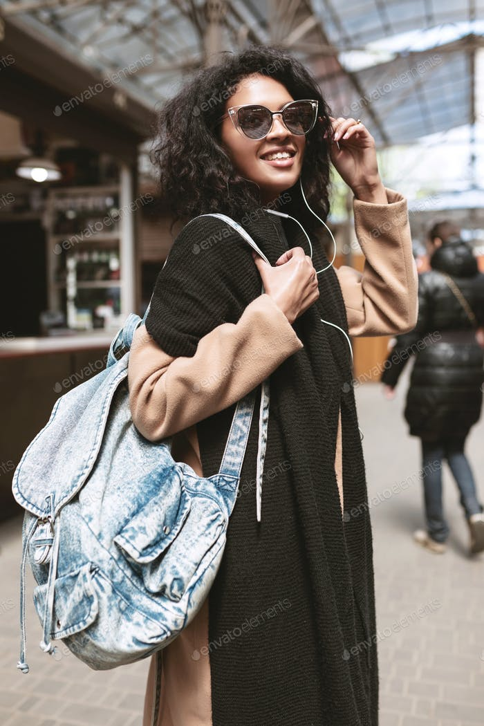 Cool girl in coat,scarf and bag on her shoulder walking around street