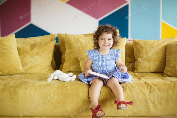 Cute little smiling girl with dark curly hair in blue dress hold