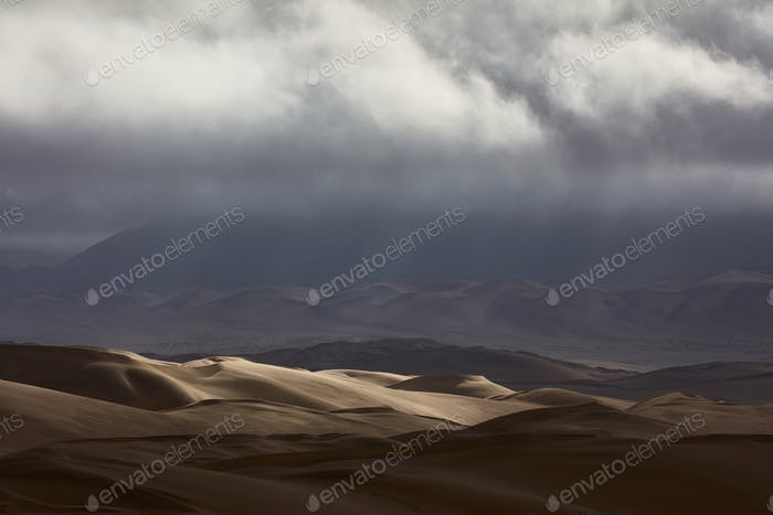 Sand dunes under a stormy sky.