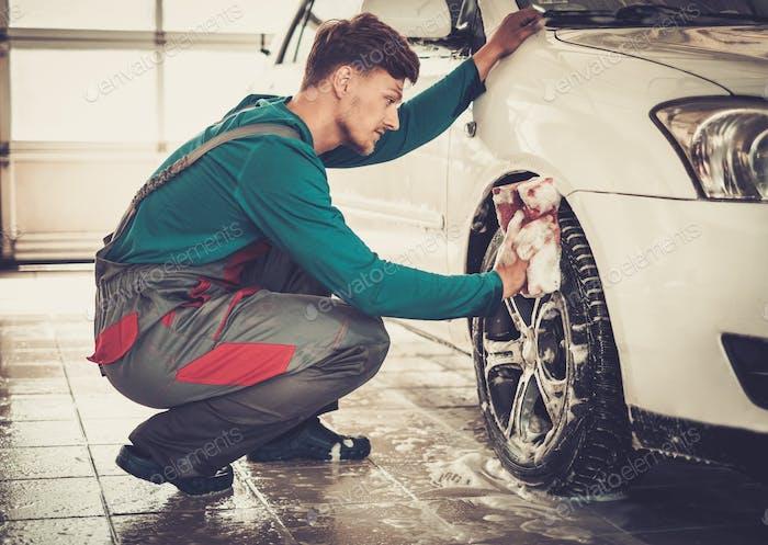 Человек работник стиральная диски сплава автомобиля на автомойке