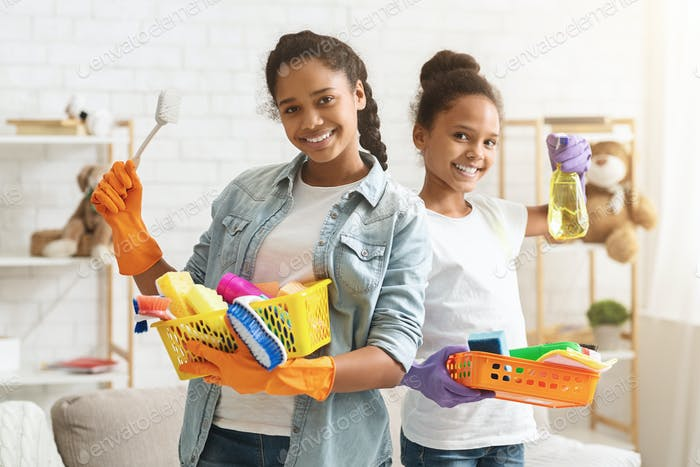 Black sisters holding cleaning stuff and smiling