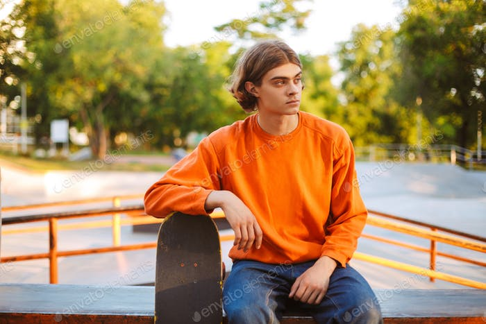 Young skater in orange pullover thoughtfully looking aside while