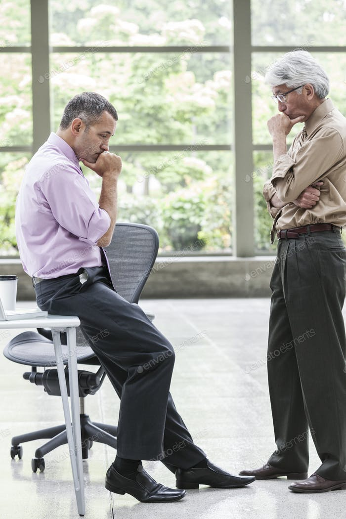 Кавказский бизнесмен и азиатский бизнесмен вместе обдумывают вопрос.