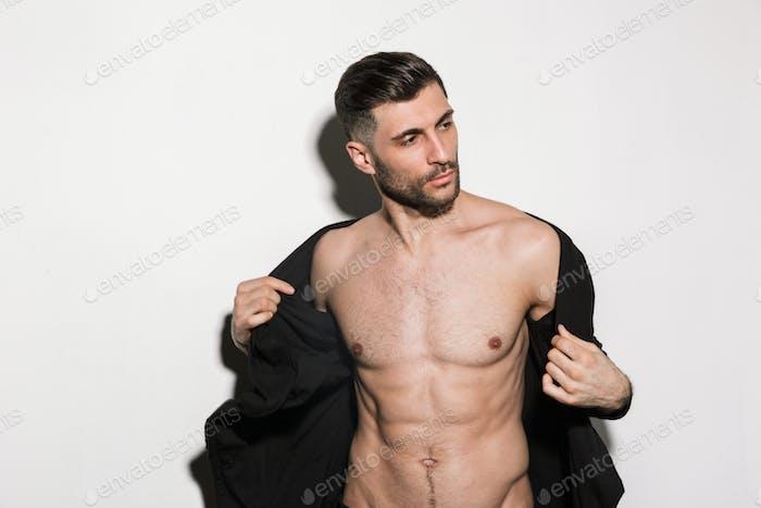 Bild von jungen bärtigen gutaussehenden sexuellen Mann zeigt seine Sixpack Körper