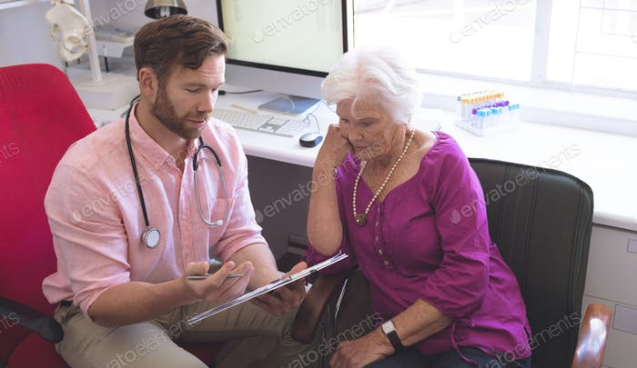 Front view of a Caucasian male doctor showing prescription to senior woman in clinic room
