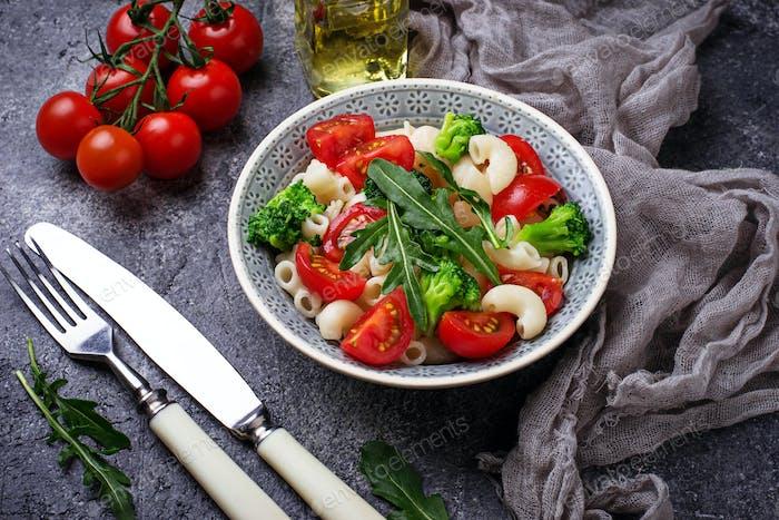 Salad with pasta, tomatoes, broccoli and arugula