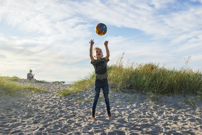 Boy (4-5) tossing ball on beach
