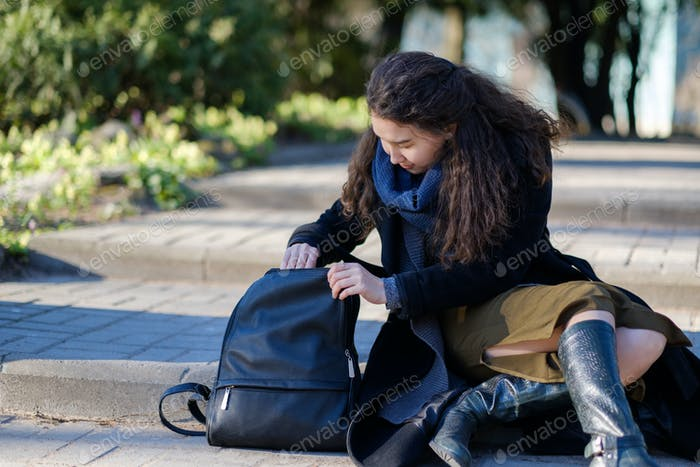 A girl with long hair is sitting on the steps and trying to find the right things in her bag.
