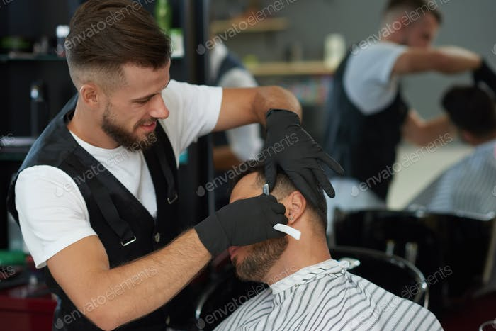 Professional barber shaving face of client with razor