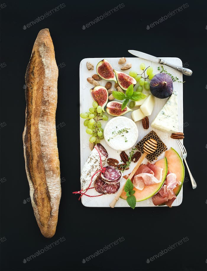 Wine and snack set. Baguette, figs, grapes, nuts, cheese variety, meat appetizers, herbs