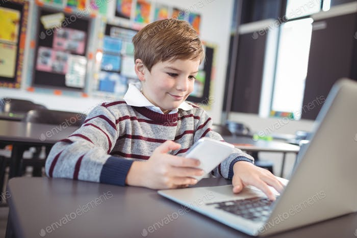 Smiling schoolboy using laptop and mobile phone on desk at classroom