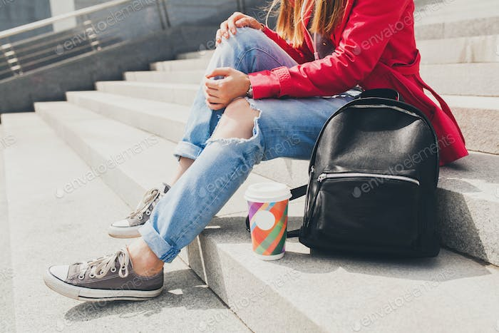 young hipster woman in pink coat, jeans sitting in street with backpack