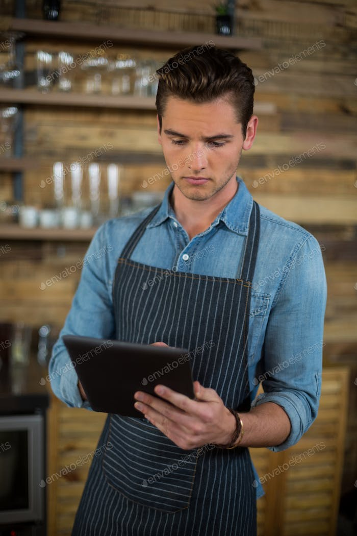 Waiter using digital tablet in café